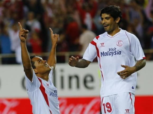 Sevilla's Carlos Bacca celebrates next to Ever Banega after scoring against Villarreal during their soccer match in Seville